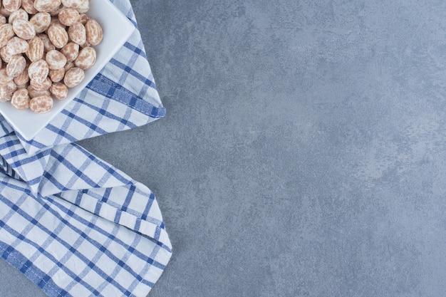Wyśmienite cukierki cynamonowe w talerzu, na marmurowym tle.