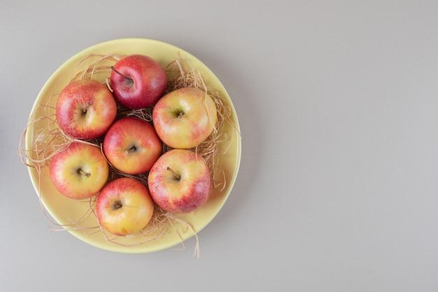 Wyśmienite jabłka i słoma w misce na marmurze