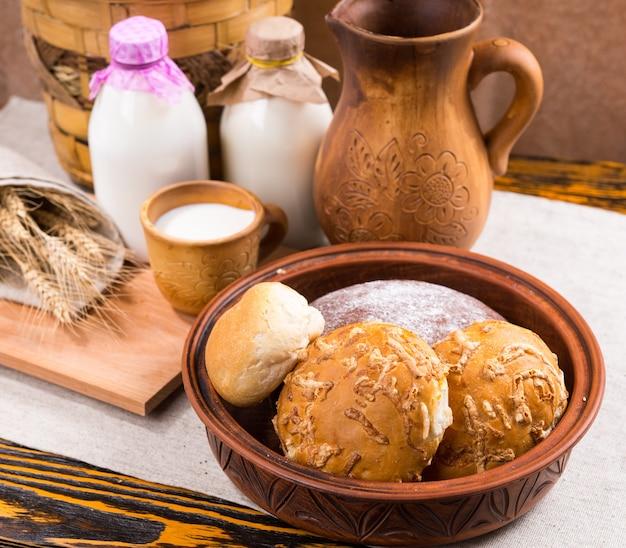 Wyśmienite, świeżo upieczone bułeczki z serem i świeżym mlekiem w naczyniach ceramicznych na zdrowe śniadanie w gospodarstwie