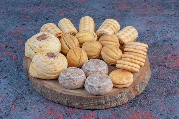 Wyśmienity asortyment ciasta na drewnianej desce na abstrakcyjnym stole.