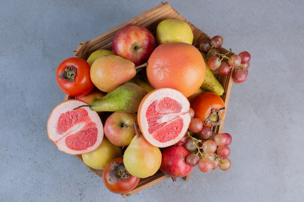 Wyśmienity asortyment owoców w drewnianym koszu na marmurowym tle.