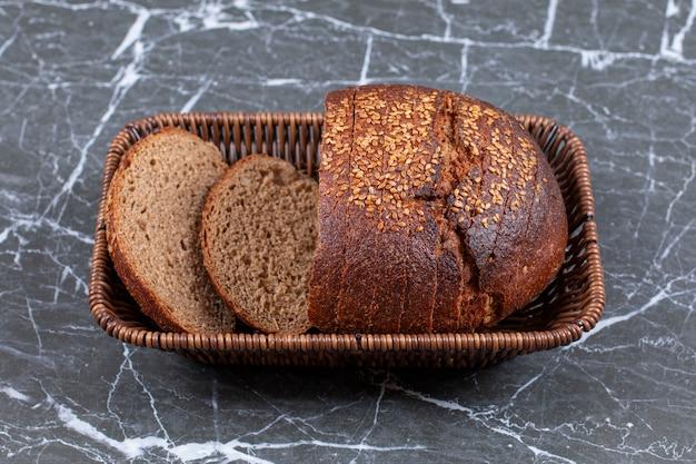 Wyśmienity chleb w koszyku, na marmurowej powierzchni