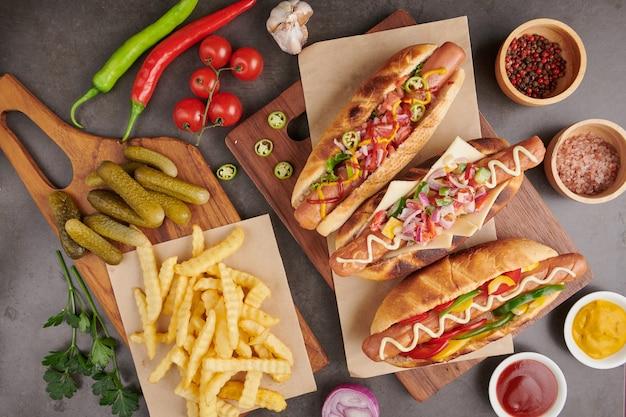Wyśmienity grillowany cały hot dog wołowy z dodatkami i frytkami. pyszne i proste hot dogi z musztardą, papryką, cebulą i nachos. hot dogi w pełni załadowane różnymi dodatkami na desce do wiosła.