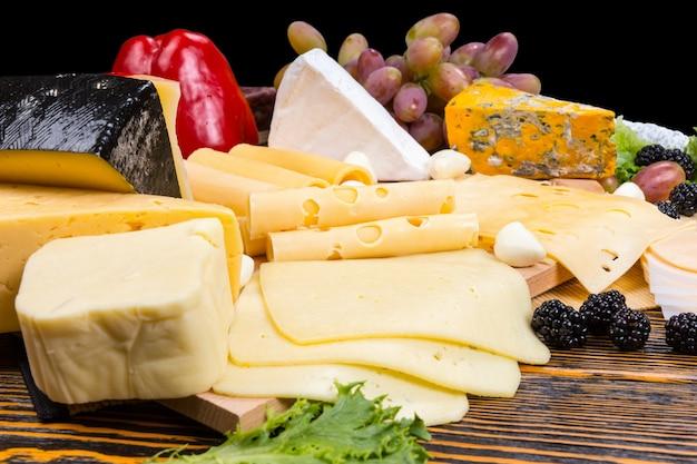 Wyśmienity wybór serów na desce serów przyozdobionych świeżymi jeżynami, oliwkami, winogronami i czerwoną papryką