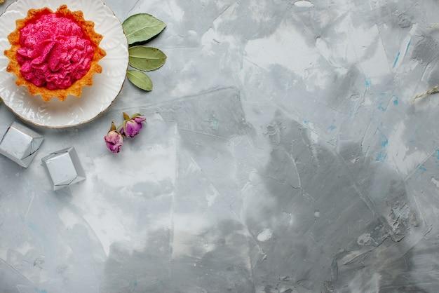 Wyśmienity wypiekany tort z różową śmietanką i czekoladkami na szarym, ciasto biszkoptowo słodki krem do pieczenia