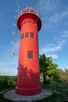 Wysoka czerwona latarnia morska przy słonecznej pogodzie. jest na betonie. na górze są różne anteny. niebieskie niebo.