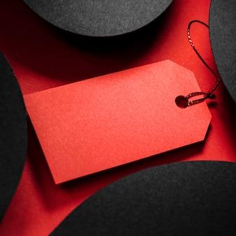 Wysoka czerwona metka z ceną i abstrakcyjne czarne kształty