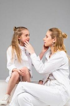Wysoka, długowłosa kobieta ze srebrną biżuterią i białymi ubraniami obserwuje swoją młodą przyjaciółkę i dotyka jej policzka