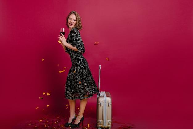 Wysoka elegancka dziewczyna świętuje wakacje z winem i śmiejąc się