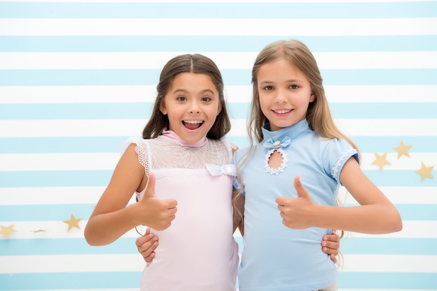 Wysoka jakość. małe dziewczynki pokazują kciuki w górę jako symbol wysokiej jakości. powodzenie. małe dziewczynki są najlepszymi przyjaciółkami.