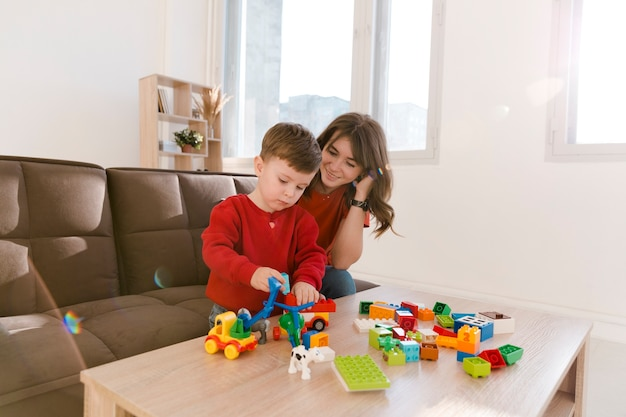 Wysoka kąt mama i syn bawią się zabawkami