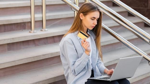 Wysoka kąt młoda kobieta kupuje online