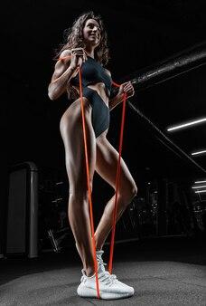 Wysoka kobieta lekkoatletycznego pozowanie z gumkami gimnastycznymi na siłowni