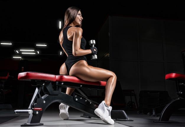 Wysoka kobieta lekkoatletycznego siedzi na ławce w siłowni z hantlami. widok z tyłu.