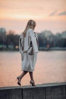 Wysoka kobieta w butach i płaszczu spacerująca w pobliżu rzeki