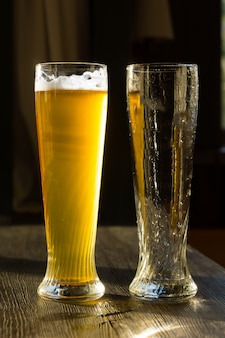 Wysoka szklanka piwa obok pustej szklanki na drewnianym stole w słońcu