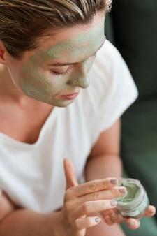 Wysoka widok kobieta stosuje organicznie twarzową maskę