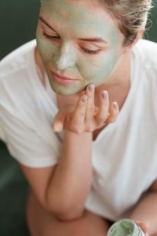 Wysoka widok kobieta stosuje twarzową maskę indoors