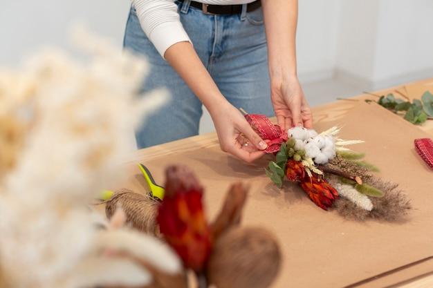 Wysoka widok kobieta układa piękny bukiet kwiatów
