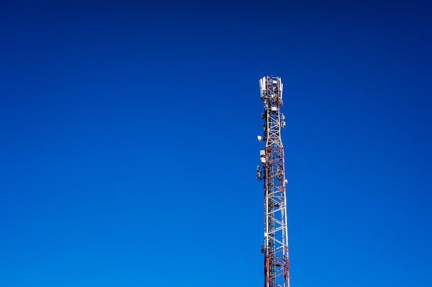 Wysoka wieża telekomunikacyjna z antenami do telefonów komórkowych tworzącymi komórki radiowe