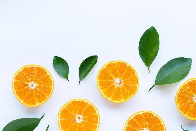 Wysoka witamina c, pomarańczowe owoce z liśćmi na białym tle.