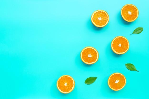 Wysoka witamina c, soczysta i słodka. świeża pomarańczowa owoc na błękitnym tle.