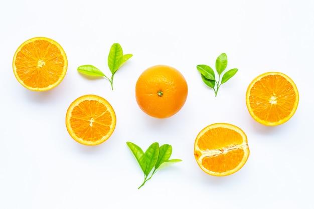 Wysoka witamina c, soczysta i słodka. świeża pomarańczowa owoc z zielonymi liśćmi na bielu.