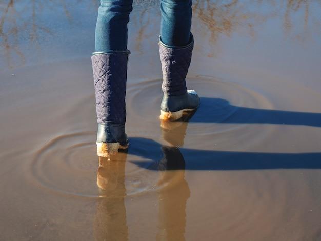 Wysoka woda, wiosną topnieje lód, kobieta spaceruje po kałużach na ulicy, wiosenna pogoda.
