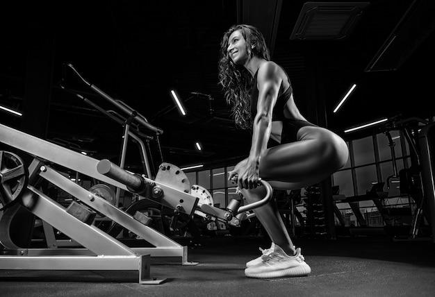 Wysoka wysportowana kobieta kuca na siłowni w specjalnym aparacie. martwy ciąg.