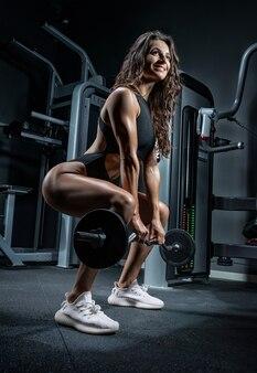 Wysoka wysportowana kobieta uśmiecha się i kuca ze sztangą na siłowni. martwy ciąg.