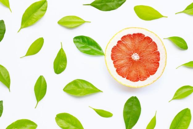 Wysoka zawartość witaminy c. soczysty grejpfrut z liśćmi. skopiuj miejsce