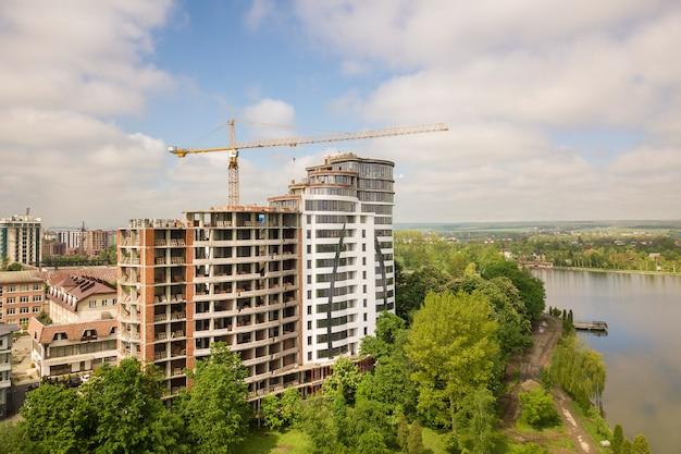 Wysoki budynek mieszkalny lub biurowy niedokończony w budowie wśród zielonych wierzchołków drzew. żurawie wieżowe na jasne błękitne niebo.