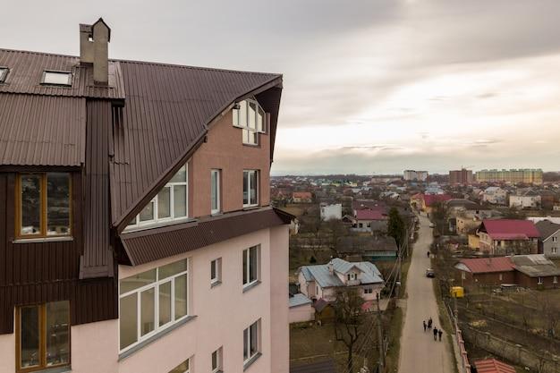 Wysoki budynek mieszkalny z wieloma oknami i dachem z blachy.
