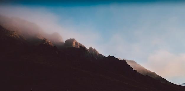 Wysoki islandzki lub szkocki krajobraz górski z wysokimi szczytami i dramatycznymi kolorami