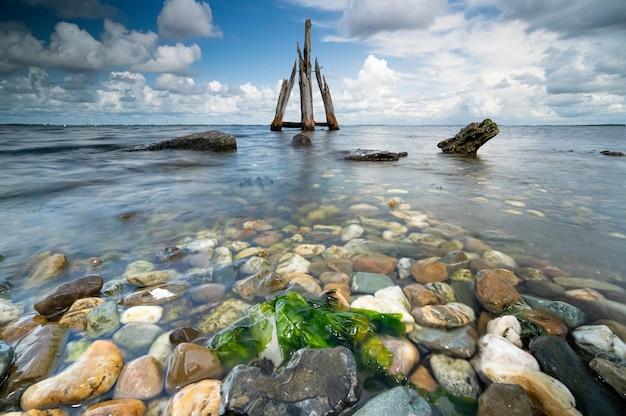 Wysoki k? t bliska strza? z kamieni nad brzegiem morza przy spokojnym morzu w tle