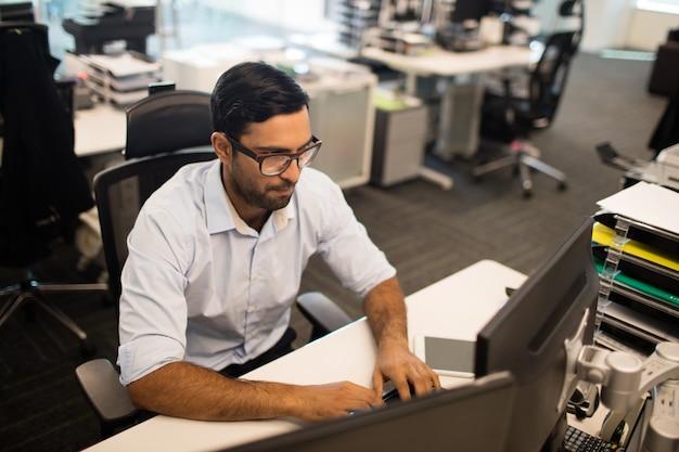 Wysoki k? t widzenia biznesmen pracuj? cy na komputerze