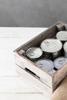 Wysoki kąt aluminiowych puszek w drewnianej skrzyni z miejscem na kopię