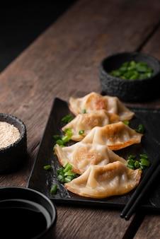 Wysoki kąt azjatyckiego naczynia na talerzu z ziołami