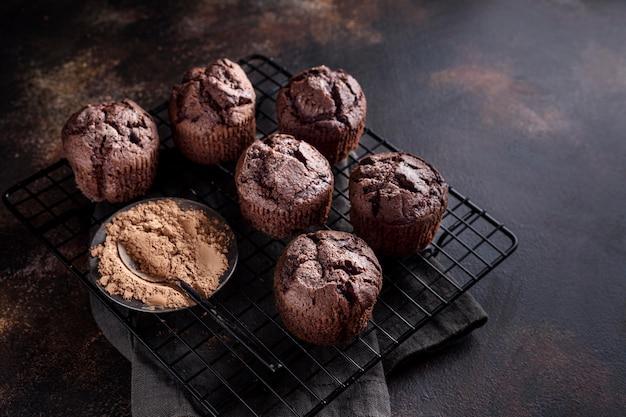 Wysoki kąt babeczek czekoladowych na stojaku chłodzącym z proszkiem kakaowym
