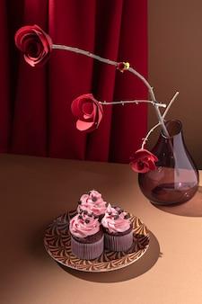 Wysoki kąt babeczki na talerzu i papierowych różach