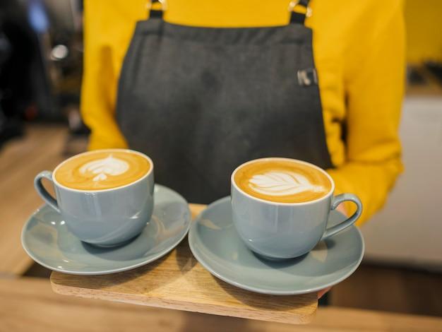 Wysoki kąt baristy trzymając filiżanki kawy