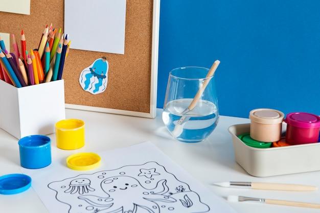 Wysoki kąt biurka dziecięcego z farbą i rysunkiem