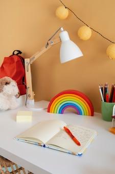 Wysoki kąt biurka dziecięcego z tęczą i notatnikiem