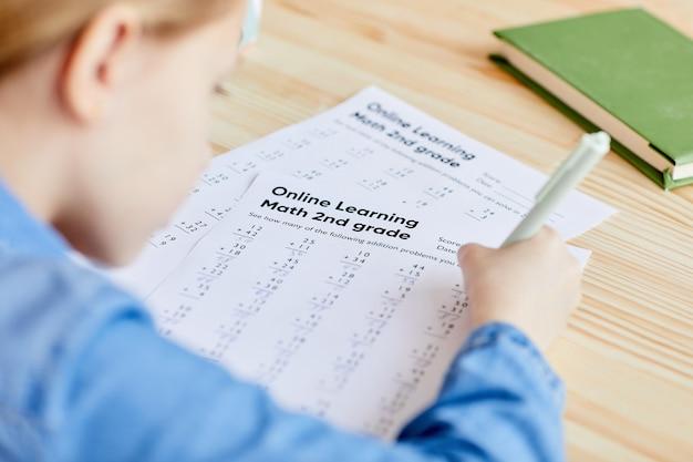 Wysoki kąt bliska nierozpoznawalnej dziewczynki robi test z matematyki w szkole online podczas nauki w domu, miejsce na kopię