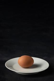 Wysoki kąt brązowe jajko na talerzu z kopiowaniem miejsca