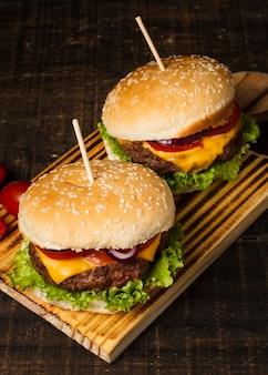 Wysoki kąt burgerów na drewnianej tacy