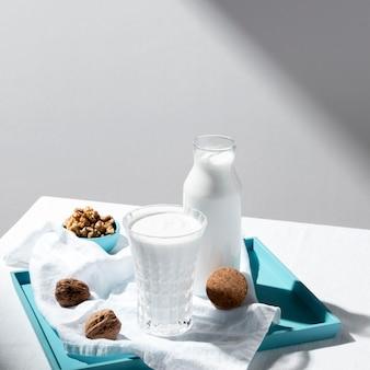 Wysoki kąt butelki mleka i szklanki z orzechami włoskimi