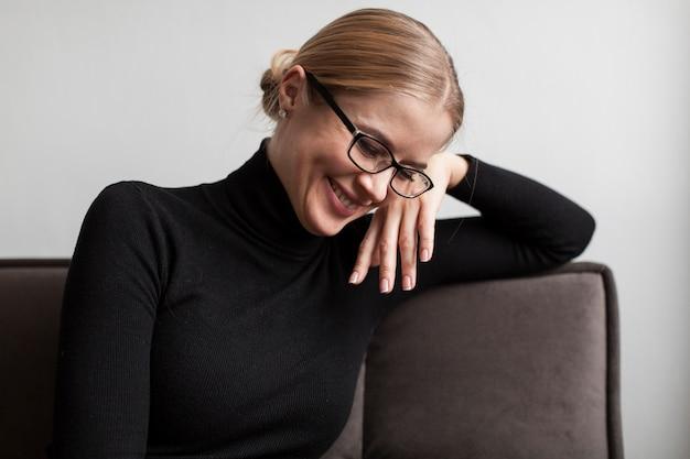 Wysoki kąt buźkę kobieta siedzi na kanapie