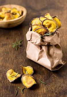 Wysoki kąt chipsów ziemniaczanych w papierowej torbie z rozmarynem