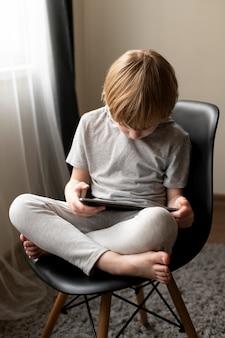 Wysoki kąt chłopca siedzącego w char i za pomocą tabletu